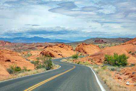 Valley of fire highway Nevada, USA. Empty winding road, passing through American desert and valley red rocks, Blue cloudy sky background