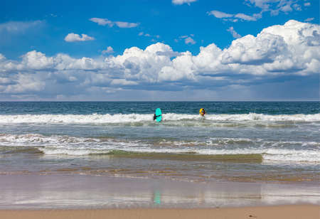 Surfers holding colorful surfboards approaching the sea ocean waves, cloudy blue sky in a sunny spring day Stock Photo