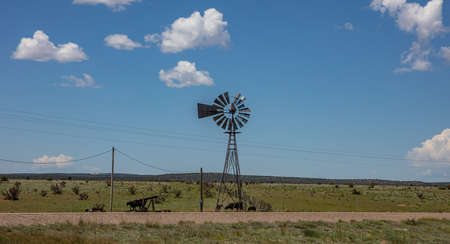 Old fashioned windmill in an american countryside landscape. Sunny spring day, rural scene, cows in a pasture, blue sky with clouds. New Mexico desert, USA Фото со стока