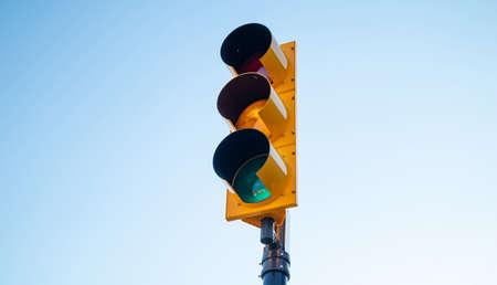サインを行く。車のための緑の信号、青い空の背景 写真素材