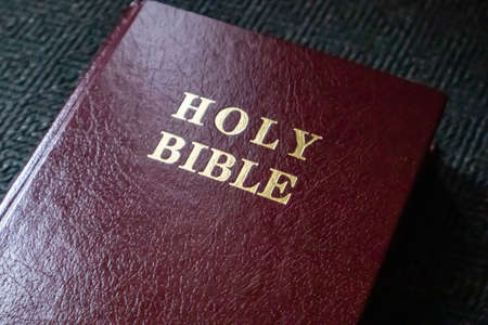Holy Bible gold text on a leather cover book red brown color, close up view. Glowing light on the book
