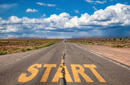 Start, new beginning concept. Text sign on a long straight highway in the american desert, blue cloudy sky background Stock Photo