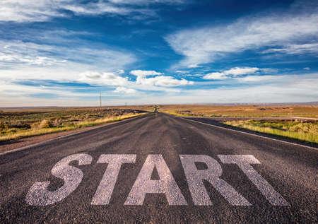 Inizio, nuovo concetto di inizio. Segno di testo su una lunga autostrada diritta nel deserto americano, sfondo blu con cielo nuvoloso