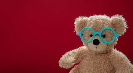 Smart kid, cute teddy wearing blue color eyeglasses against red background, copy space. Back to school, eyesight test
