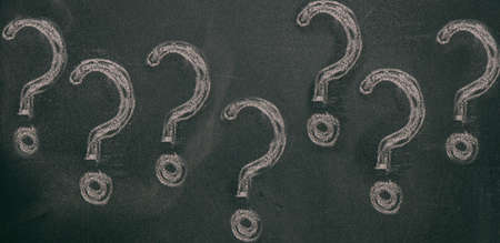 Question marks chalk drawing on blackboard background. Confusion, problem concept