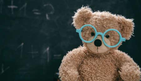 Back to school. Smart kid in class, cute teddy wearing blue eyeglasses against blank chalk blackboard, copy space. Imagens