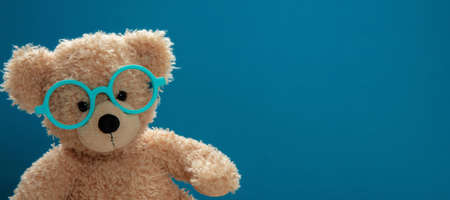 Back to school, eyesight test. Smart kid, cute teddy wearing eyeglasses against blue color background, banner, copy space.