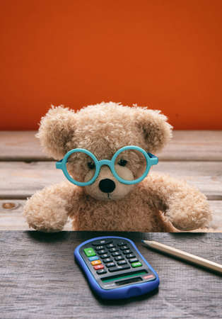 Back to school, Maths concept. Smart kid cute teddy wearing blue eyeglasses working with a calculator on his desk, orange color background Stock Photo