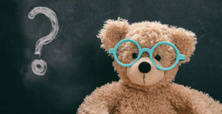 Confused child, doubt. Smart kid in class, question mark on blackboard, cute teddy wearing blue eyeglasses Imagens