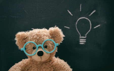 Bright idea, solution. Smart kid cute teddy wearing blue eyeglasses in class, lightbulb sketch on blackboard,