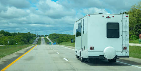 RV recreational vehicle rear view on the highway, cloudy sky. USA countryside