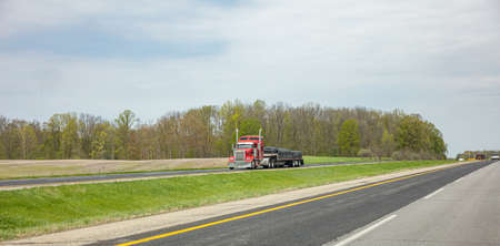 Truck red color with trailer on the highway, cloudy sky, USA countryside Archivio Fotografico