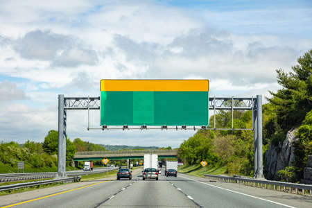 Blank road sign on the highway, cloudy blue sky background, copy space. US of America.
