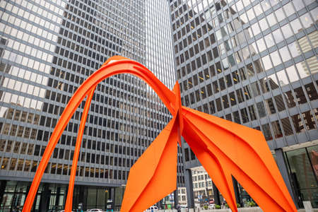 Chicago, Illinois, USA. May 9, 2019. Red Flamingo art sculpture between office buildings exterior at Federal Plaza, Skyscrapers with mirror windows background.