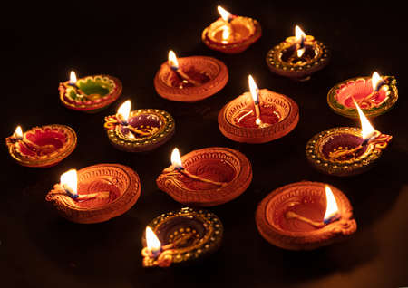 Happy Diwali. Clay diya candles illuminated in Dipavali, Hindu festival of lights. Traditional oil lamps on dark background, closeup view
