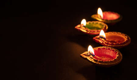 Diwali, Hindu festival of lights. Clay diyas candles illuminated in Dipavali. Oil lamps on traditional tray, copy space