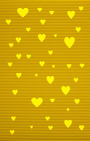 Love concept. Yellow color corrugated cardboard paper and hearts background and texture