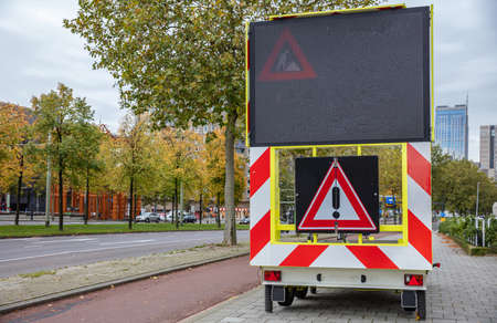 Roadworks warning signage, led lights board and danger exclamation traffic sign on a trailer in the city center, cloudy autumn day Stock Photo