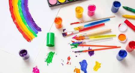 Créativité des enfants, dessin arc-en-ciel. Ensemble de peintures au doigt colorées et pinceaux sur fond de couleur blanche, vue de dessus