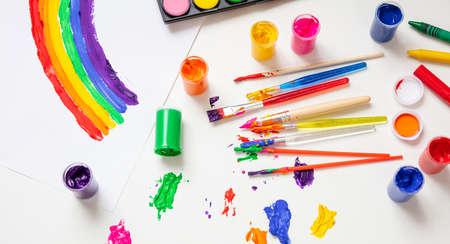Kinderkreativität, Regenbogenzeichnung. Bunte Fingerfarben-Set und Pinsel auf weißem Hintergrund, Ansicht von oben
