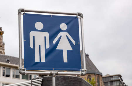 WC toilets sign. Mobile toilets signage in the city for an outdoors event, cloudy sky background. Square metal frame and blue fabric with human silhouettes