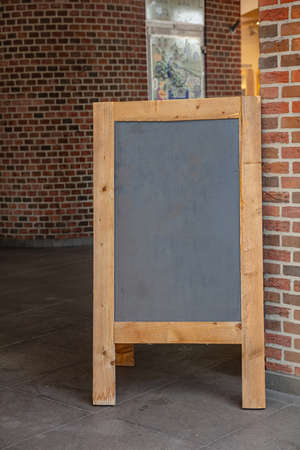 Menu template, Blackboard blank with wooden frame outdoors on a sidewalk, copy space