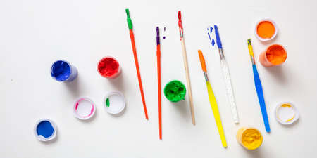 Kids creativity. Colorful finger paints set and paint brushes on white color background, top view 版權商用圖片