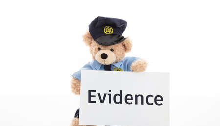 Police and evidence concept. Cute teddy bear in police officer uniform holding a card with evidence text isolated against white background Stock Photo