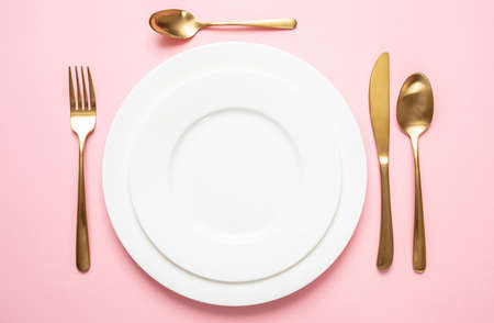Luxuriöse Tischdekoration in Gold und Rosa. Goldenes Besteckset und weißes Geschirr vor rosafarbenem Hintergrund. Ansicht von oben, Textfreiraum