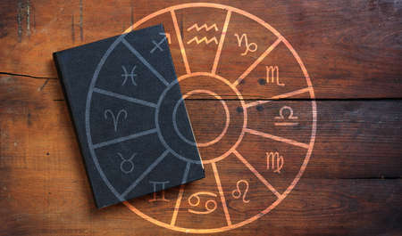 Astrology and horoscopes concept. Black book and astrological zodiac signs wheel on wood background. Stock Photo
