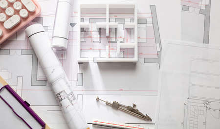 Female architect engineer office desk. Blueprint plans,  building project architectural design and a pink computer keyboard