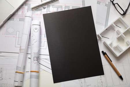 Architect engineer office desk. Blueprint plans, blank black carton paper and office supplies, copy space, top view Foto de archivo - 133734204