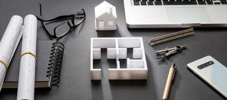 Architect engineer office desk. Blueprint plans and house model, Residential building project in black and white, banner Foto de archivo - 133734214