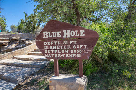 Santa Rosa, New Mexico, USA. May 14, 2019. The wooden sign on the rock inform about the Blue Hole, the famous deep pool, for the depth and the water temperature.