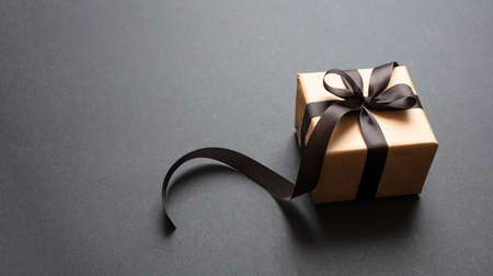 Black Friday sale concept. Gift box with black ribbon isolated against black background, high angle view 版權商用圖片 - 134777785