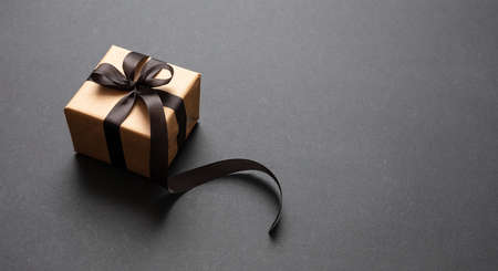 Black Friday sale concept. Gift box with black ribbon isolated against black background, high angle view