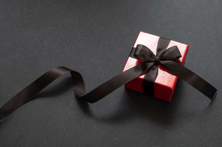 Black Friday sale concept. Red color gift box with black ribbon isolated against black background, high angle view 版權商用圖片 - 134777774