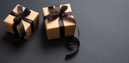 Black Friday sale concept. Gift boxes with black ribbon isolated against black background, high angle view 版權商用圖片 - 134777776