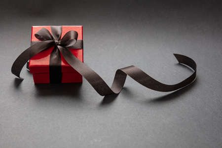 Black Friday sale concept. Red color gift box with black ribbon isolated against black background, high angle view 版權商用圖片