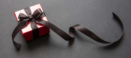 Black Friday sale concept. Red color gift box with black ribbon isolated against black background, banner, high angle view