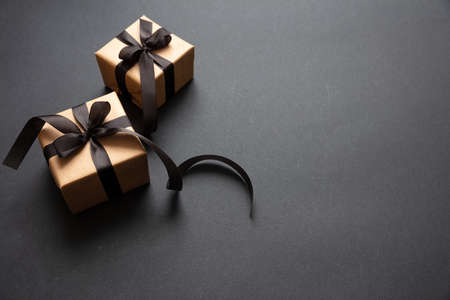 Black Friday sale concept. Gift boxes with black ribbon isolated against black background, high angle view Stock Photo