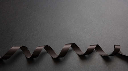 Black ribbon curly on black color background, copy space. Minimal black card template Stock Photo