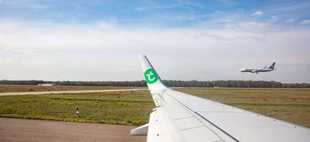 Eindhoven Netherlands. October 14, 2019. Transavia plane on the runway at Eindhoven airport, ready for take off while Ryanair plane is landing. View out of airplane window. Editorial