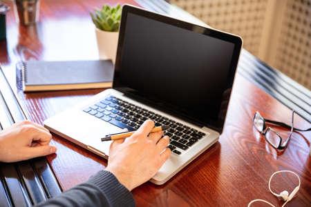 Computer screen mockup. Laptop with black blank screen on a wood desk, office background, copy space Zdjęcie Seryjne