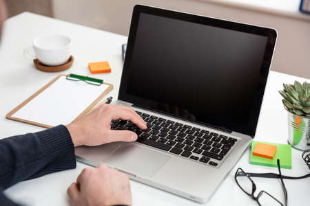 Computer screen mockup. Man working with a black blank screen laptop on a wood desk, office background, copy space Zdjęcie Seryjne