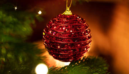 Christmas tree ornament decoration. Xmas ball red color decorated hanging on a fir branch, closeup view, glowing fire background