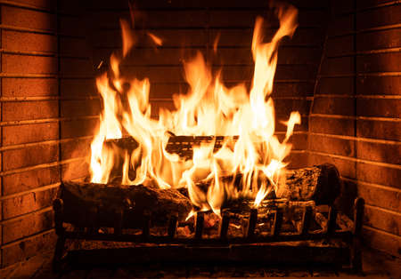 Fireplace burning with firewood logs. Christmas, winter, and travel concept. Warm cozy home Reklamní fotografie