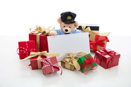 Police and christmas concept. Cute teddy bear in police officer uniform and xmas gift boxes isolated against white background, copy space