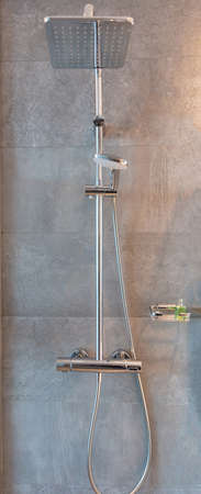 A modern shower in front of ceramic tile wall. A luxury douse bath of an apartment or a hotel. Vertical photo.