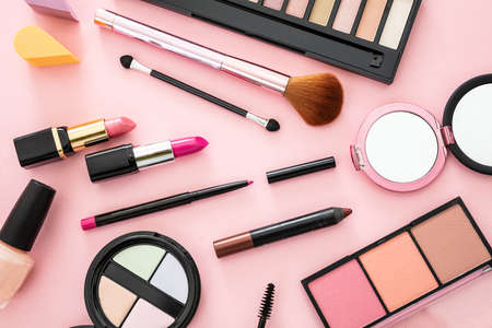 Make up cosmetics flat lay. Lipstick and nail polish, eye shadows and blush, brushes and pencils against pink color background